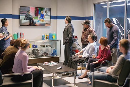 Auto shop waiting area with people watching sports on TV