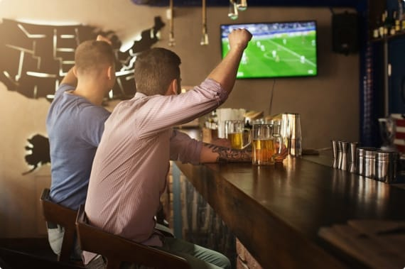 Two men cheering at while watching sports at sports bar