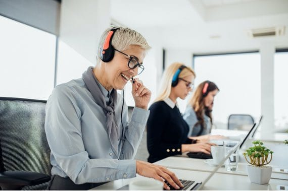 Woman in Office on Headset and Laptop