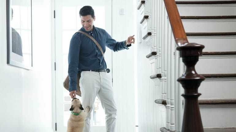 man giving his dog a treat at the front door of his home