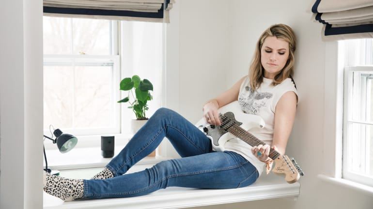 girl playing the guitar in her room