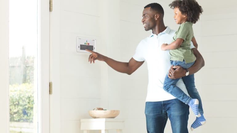 man holding child using home alarm system