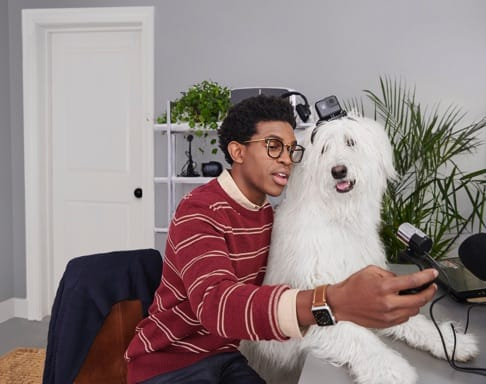 A young man is taking a picture of himself and his dog.