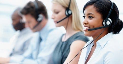 A row of employees speak to customers through a headset.