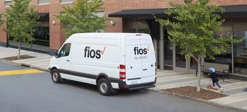 A Verizon Fios service van sits parked in front of an office building.