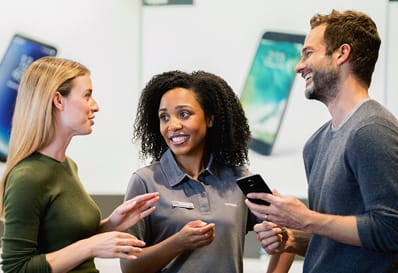 A customer service representative assists two people with a cell phone purchase.