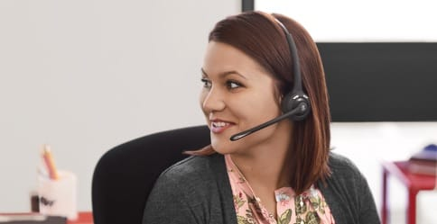 A woman speaks to a customer through a headset.