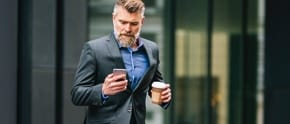 man holding phone and coffee