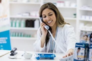 Woman in medical coat on phone in a medical office