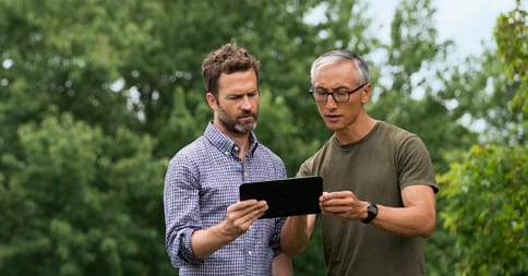Two men stand outside, concentrating on a tablet screen.