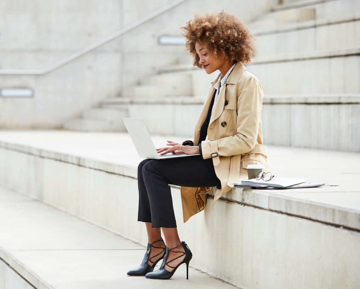 A woman sits outside on a step, working on a laptop computer.