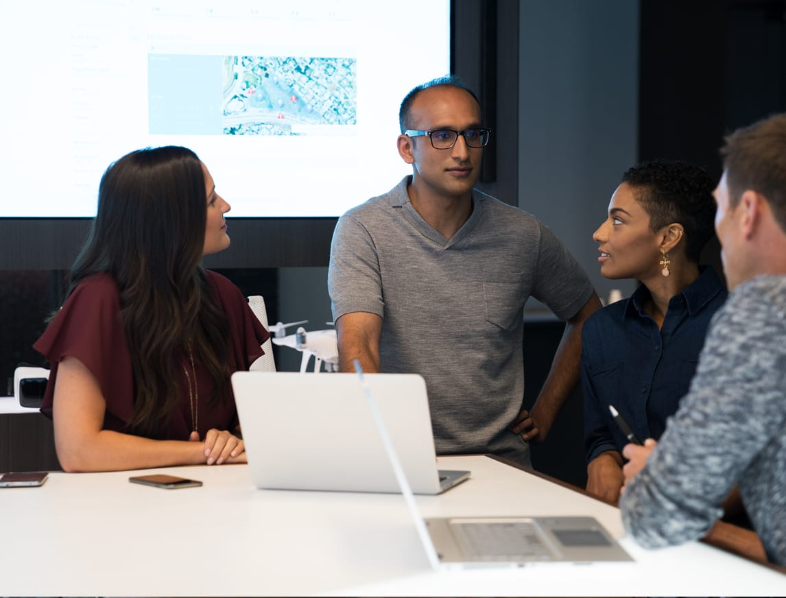 A group of coworkers converse in a conference room, an open laptop sitting on the table.
