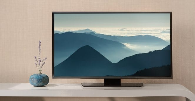 A TV monitor depicting mountains sits on a TV stand against a wall.
