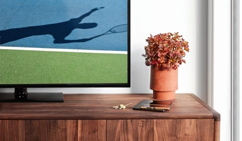 A TV monitor depicting a tennis match sits next to a vase of flowers.