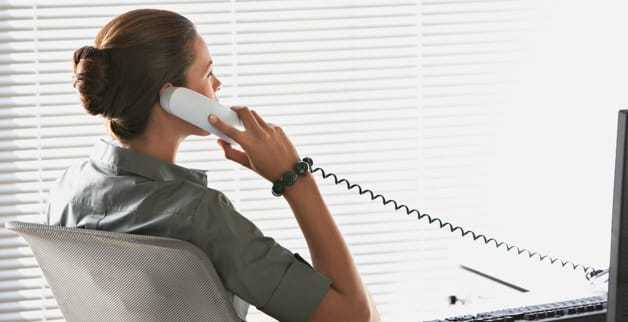 A woman leans back in a chair while speaking on a desk phone.