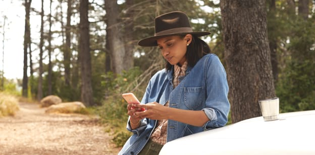 A woman leans against a truck, typing on her cell phone.