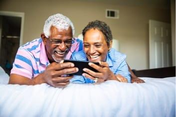 Elderly couple sharing phone