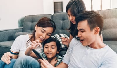 Family on couch playing game on phone