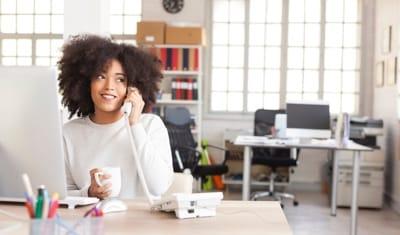 Woman talking on a landline phone at work