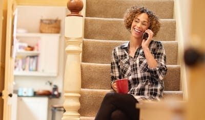 Woman sitting on stairs talking on her phone