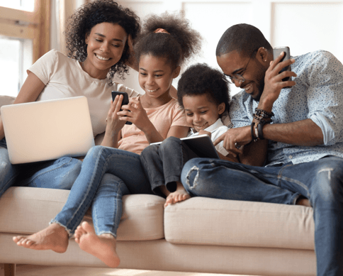 a family on a couch using different devices