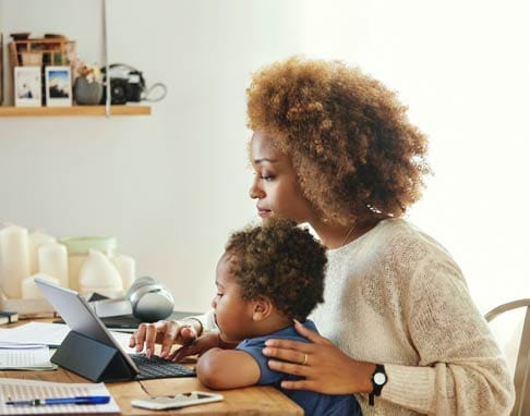 woman with child looking at a laptop