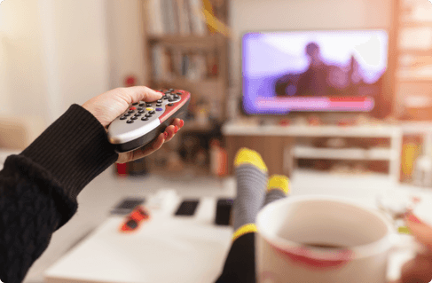 an outreached hand changing the channel with a remote