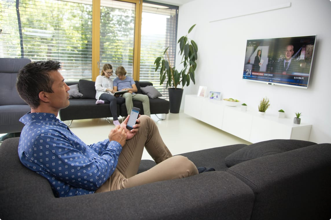 Family sittuing on couch with devices