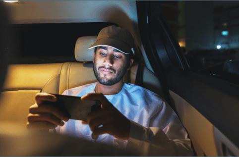 Man watching something on phone while riding in an Uber car