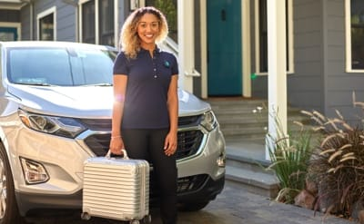a woman stands in front of a car with a rolling suitcase