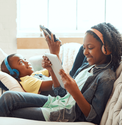 Woman on the couch with her son using tablets