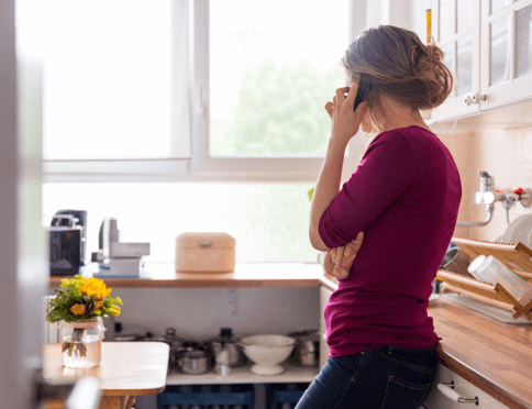 Woman in kitchen on landline phone