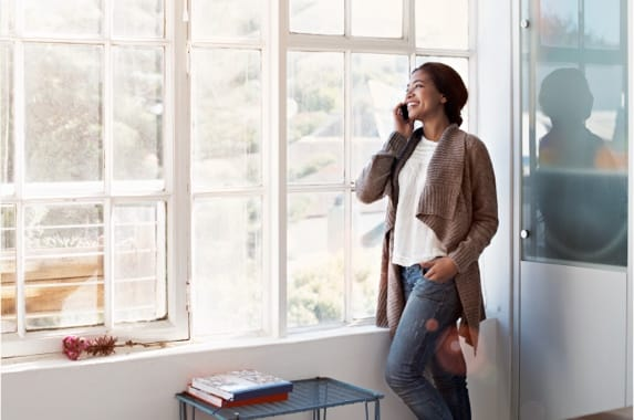 A woman on a cellphone standing by the window