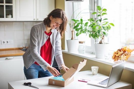 A woman opens a box next to a laptop