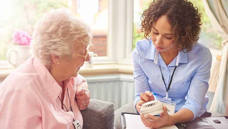 nurse showing a smoke detector to an older person