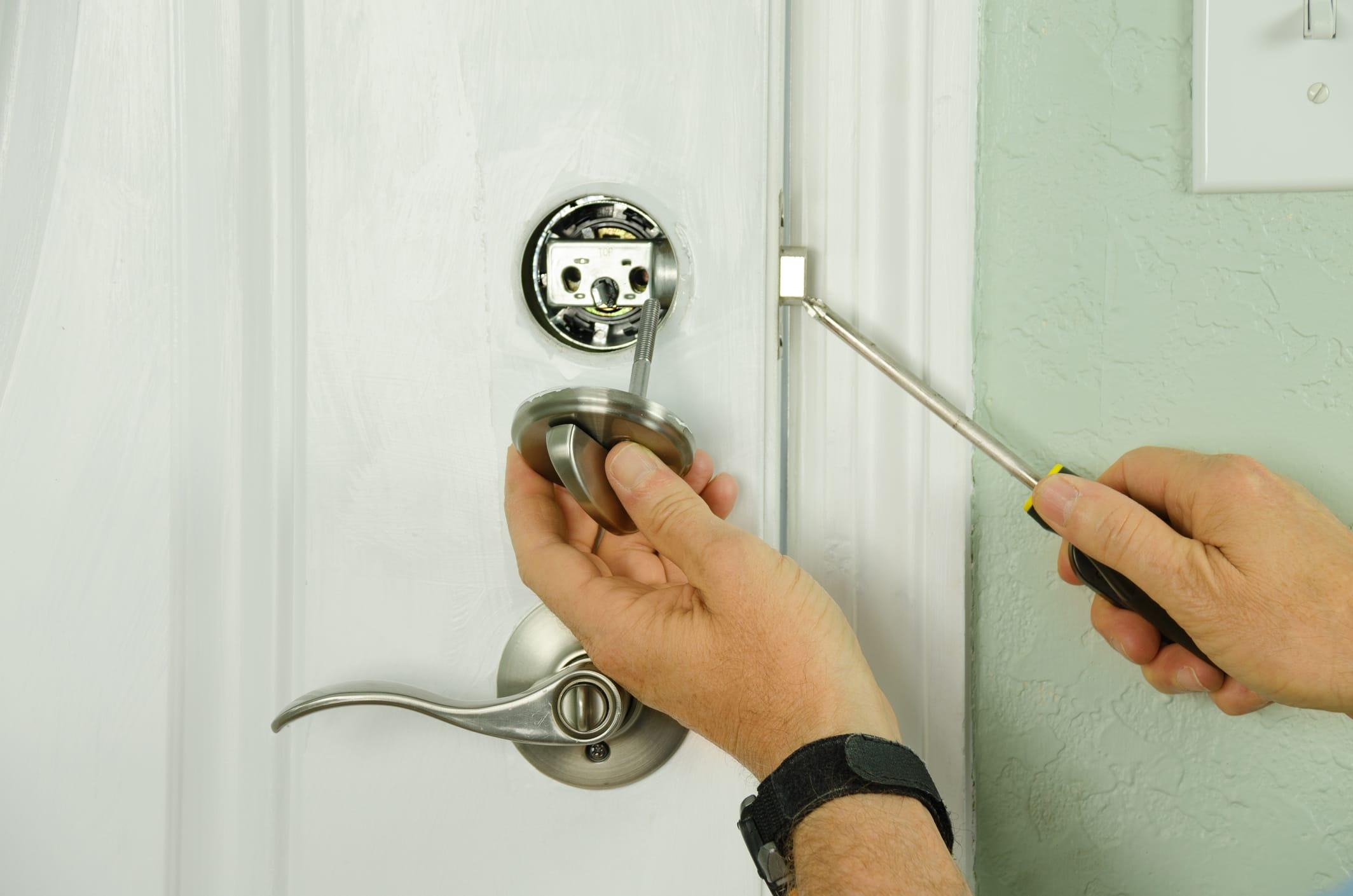 person installing door lock