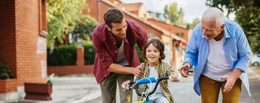 Father and grandfather teach boy to bike