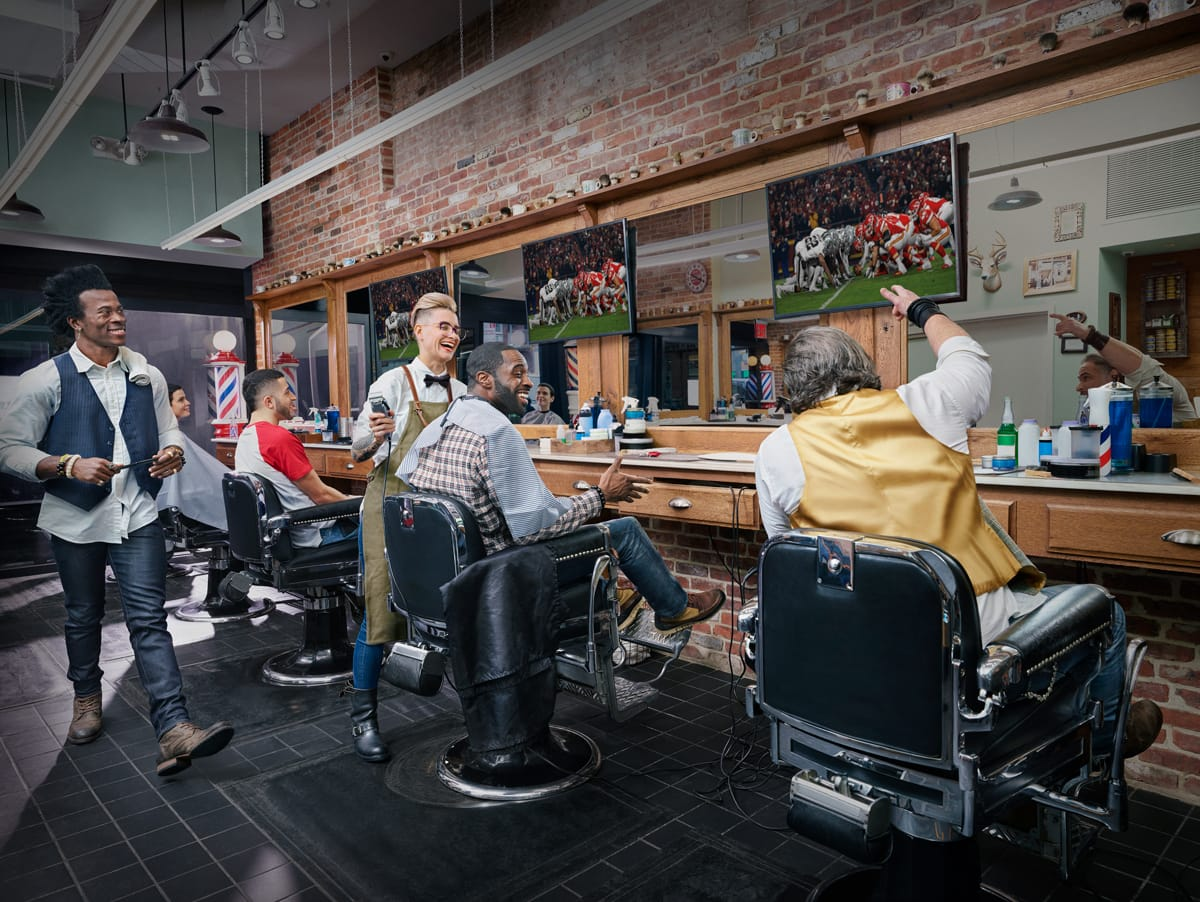 People inside a Barbershop with TV in background