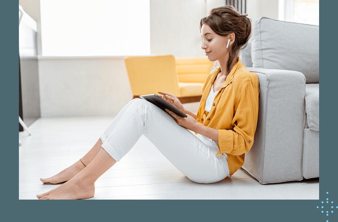woman sitting on floor using tablet