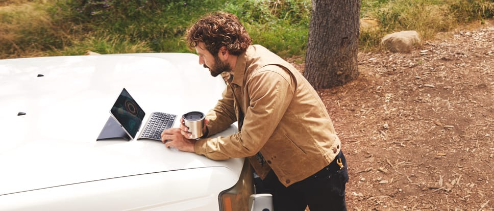A man looks at an open laptop placed on the hood of a truck.