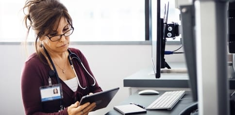 A female doctor looks down at a tablet in her hands.