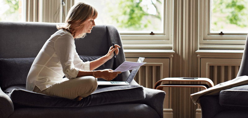Woman on couch with laptop and papers