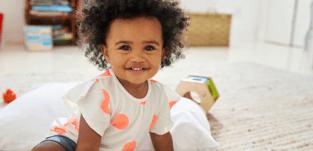 toddler sitting on floor smiling