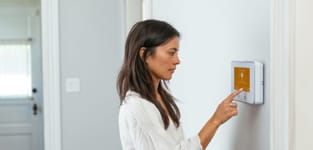 woman using vivint smart hub on the wall