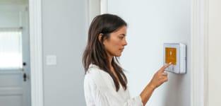 woman using vivint smart hub on the wall