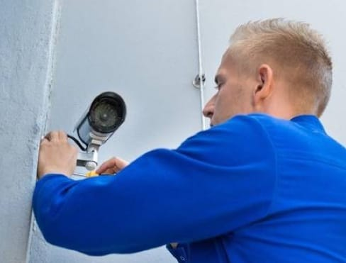 ADT home security technician installing camera