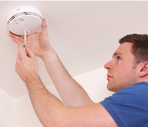 ADT home security technician installing smoke detector