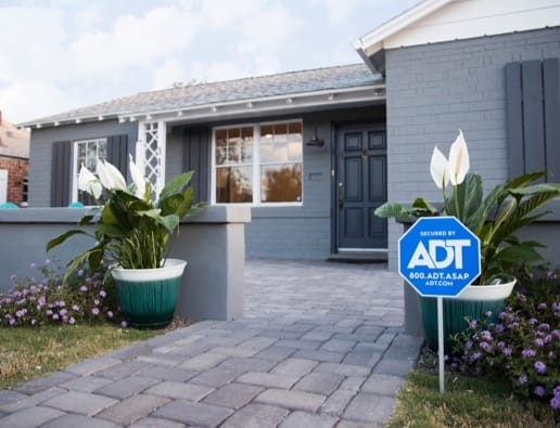 Home with an ADT sign in the front yard