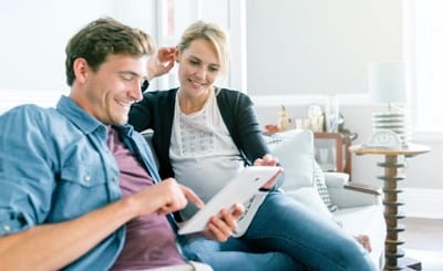 A man and a woman smile as they sit on a couch and look at a tablet screen