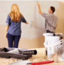 Couple painting interior home wall